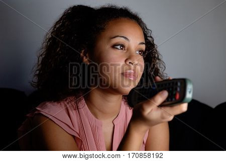 Bored woman holding television remote at night