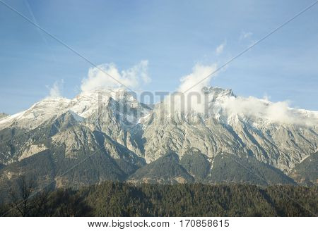 Austria - January, 2017 For forest seen huge mountain peaks, mountain ranges stretch under the sky, the snow on the tops of the mountains, the clouds in the sky, alpine mountains against the blue sky