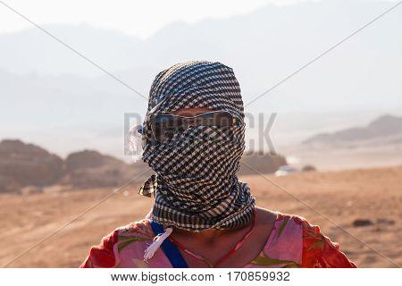 Caucasian girl in head kerchief in the desert.