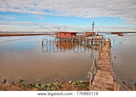 Comacchio, Ferrara, Emilia Romagna,Italy: landscape of the wetland in the nature reserve Po Delta Park with fishing huts in the lagoon