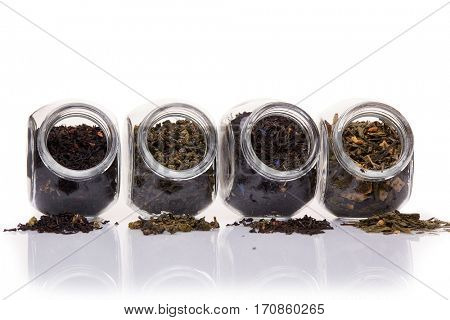 Various kinds of dry tea in glass jars lying on a white background.  Different kinds of tea leaves.