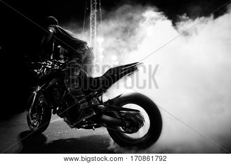 black and white motion blur of motorcycle stunt rider riding and burn wheel tire with engine power make much smoke
