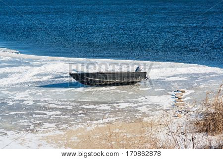 Boat with outboard motor lies on the ice-covered river bank