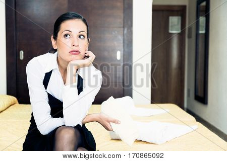 frustrated room maid sitting on bed in hotel room