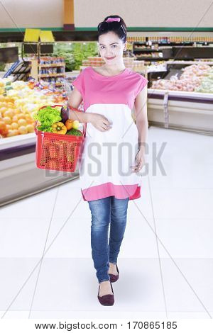 Portrait of young woman shopping vegetables while holding shopping cart in grocery