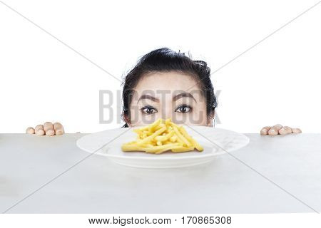 Picture of young woman peeping french fries on a plate isolated on white background