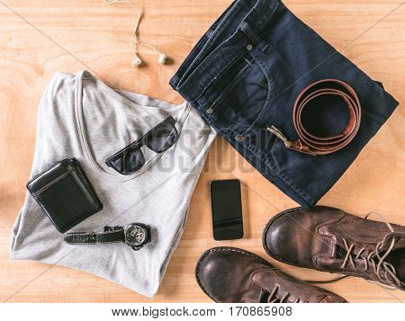 Top view of Men's casual outfits with accessories on wooden table background
