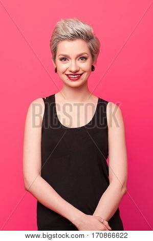 Happy blond girl with dyed hair. Smiling woman with bright makeup over pink background