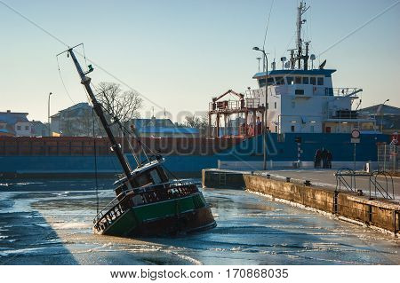 WINTER IN PORT - The ship enters a port near the sinking boat
