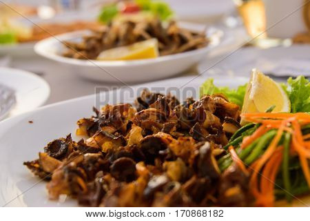 Grilled sea snails. Very tasty food on a light background.