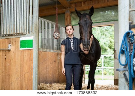 Young girl with her horse in the stable