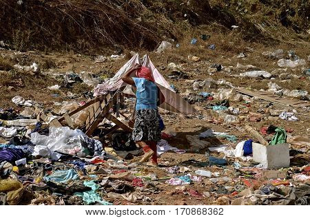 MAZATLAN, MEXICO, January 30, 2017: An unidentified lady walks to her home, shelter, or residence  in a city landfill  o0r dump located in Mazatlan, Mexico