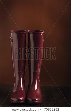 Photo in low key. Rubber boots burgundy color on a brown background. Selective focus.
