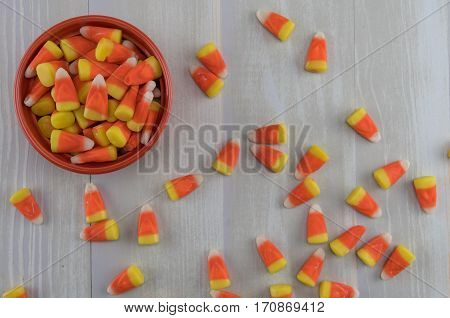Candy Corn in Orange Bowl with Mess Spill Over across gray background