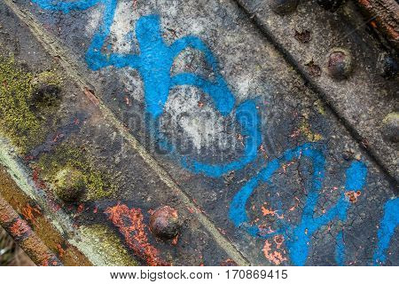 A macro shot of an old bridge trestle with rust cracked paint and moss.