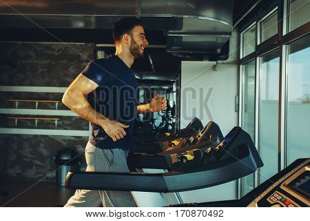 Young handsome man in sportswear running on treadmill at gym