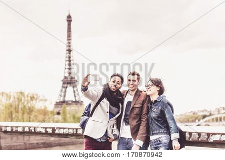 Multi-ethnic group of friends having fun in Paris along the Seine river, near Eiffel Tower.
