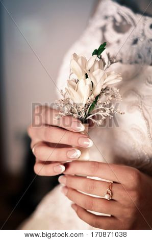 Bride in a white dress is holding a wedding bouquet in hands