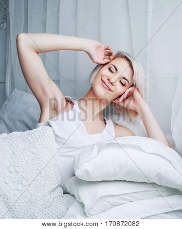 beautiful woman waking up at home in bed