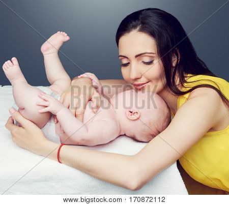 happy young mother and her sleeping baby, isolated against gray background