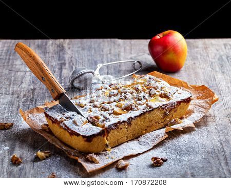 Apple pie dusted with powdered sugar on a grey background. The knife stuck into the tart. Red Apple is in the background. Selective focus