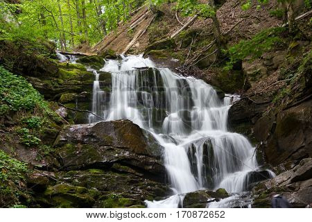 waterfall on the Carpatian mountaince, green moss and trees