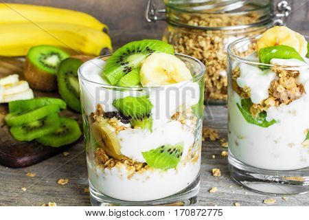 Homemade yogurt parfait with granola, kiwi fruit, banana and nuts in a glass for healthy breakfast on rustic wooden background