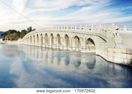 Beautiful landscape of the seventeen hole bridge with sky reflection on the water shot at the Summer Palace Beijing