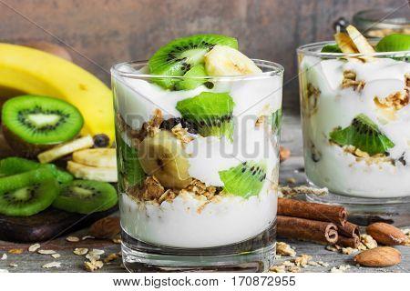 healthy breakfast. homemade yogurt parfait with granola, kiwi fruit, banana, cinnamon and nuts in glasses on rustic wooden table