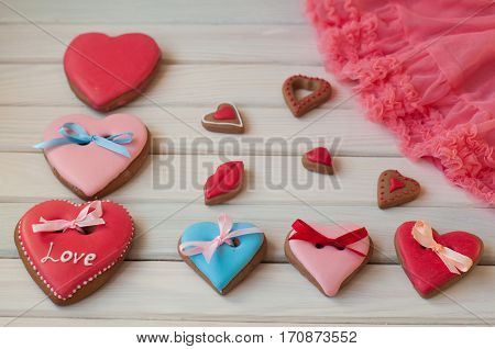 Holiday rose red blue glazed honey heart shaped cakes with ribbons lay on white wooden table near rose lace