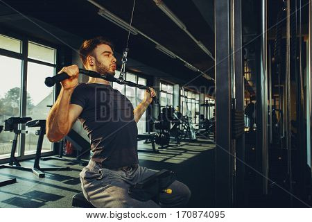 Handsome man doing heavy weight exercise for back in the gym