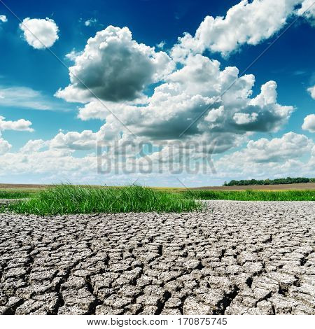 drought earth with green grass area under low dramatic clouds