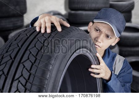 Professional mechanic checking car tyre while looking at texture of tyre in his workshop