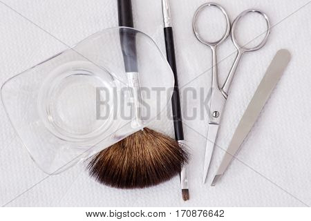 Crop of cosmetologist work place in beauty salon, tools for permanent make up of eyebrows. Working table of professional makeup artists with brushes, scissors and tweezers.