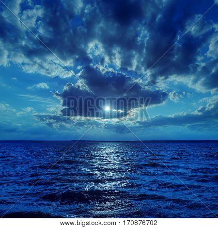moonlight in dark clouds over water