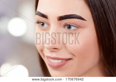 Portrait of attractive smiling girl during procedure of permanent make up of eyebrows. Pretty brunette whiting of finishing of procedure with brown paint on eyebrows. Beauty salon.