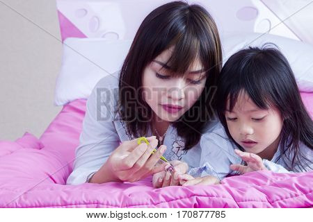 Young mother cutting nails of her daughter with a nail clipper while lying on the bed