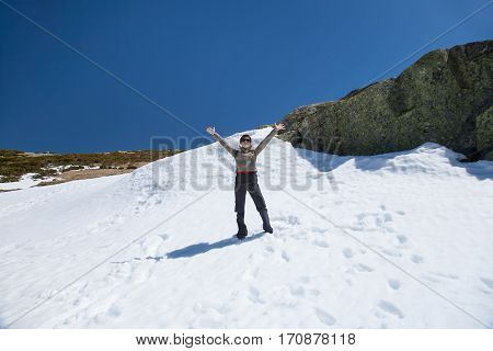 brunette sport active woman with green jacket black trousers and red backpack greeting open arms looking in snow with blue sky in Gredos mountain Avila Spain Europe