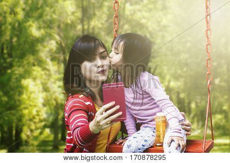 Happy young mother and her daughter taking selfie photo together while the girl kissing her mother at the park