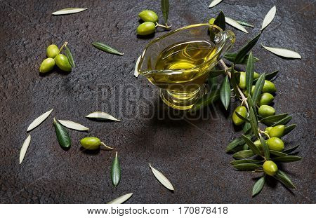 Twig of olive tree with green olives and glass sauceboat of olive oil on a black grunge metal background.
