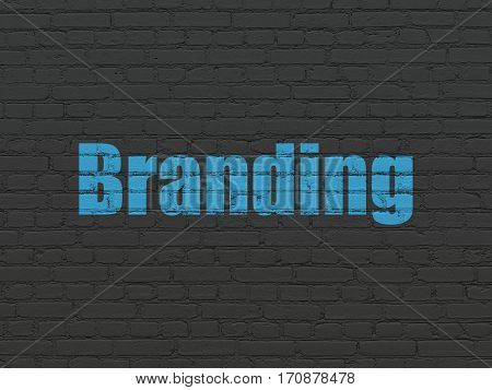 Advertising concept: Painted blue text Branding on Black Brick wall background