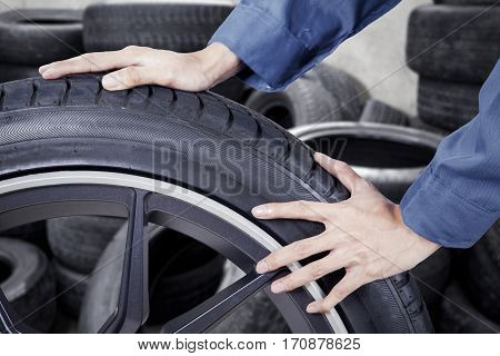 Close up of mechanic pushing black tyre in tire storage