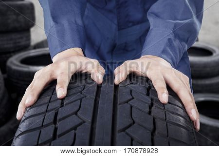 Close up of mechanic hands pushing black tyre in his workplace
