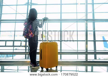 Back view of a little girl standing in the airport while looking at aircraft on the window and carrying bag