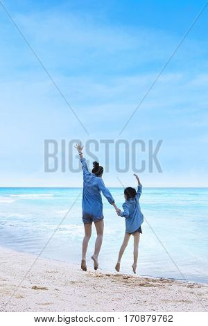 Rear view of joyful young woman and her daughter leaping together on the beach with blue sky