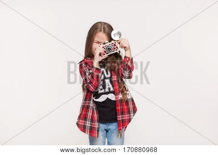 Beautiful child girl holding a instant camera. Little kid taking pictures with retro camera isolated on white background