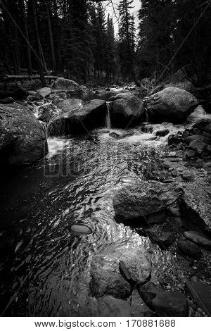 Black and white image of a river flowing over large rocks.