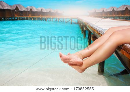Women's Legs At Wooden Pier Of Tropical Island Resort