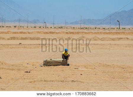 SHARM EL SHEIKH EGYPT - JULY 9 2009. a man sitting in the desert.