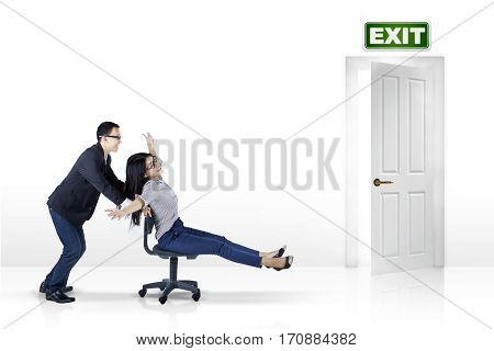Picture of female entrepreneur sitting on the chair and moving fast helped by her partner toward exit door isolated on white background